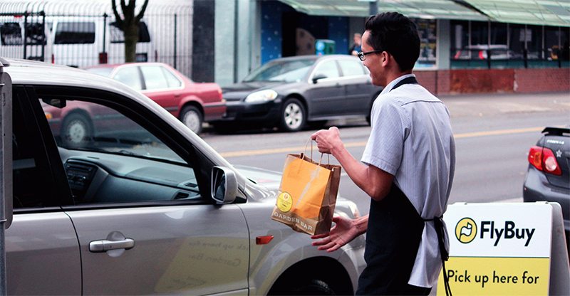 A store staff delivering product at curbside pickup point
